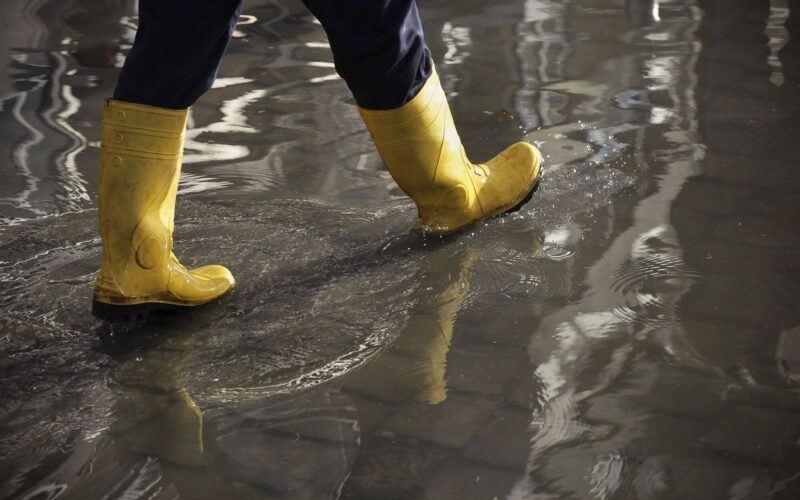 seguro cobre enchente: bota de plástico andando em ambiente alagado